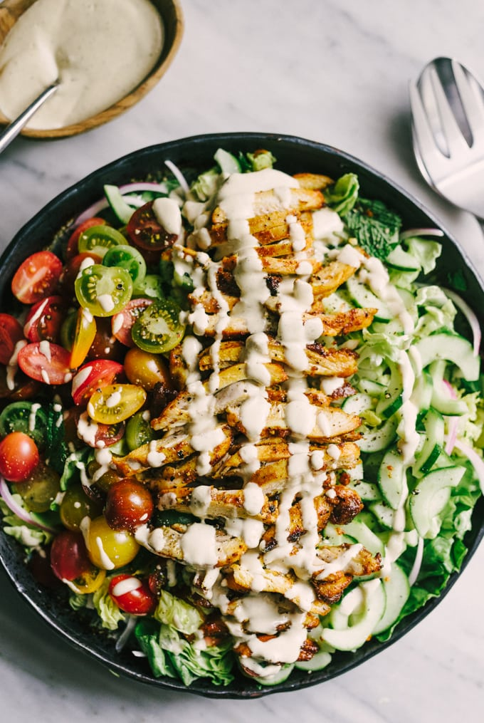 A large bowl of chicken shawarma salad with crunchy lettuce, fresh herbs, sliced cucumbers, and fresh tomatoes drizzled with tahini dressing.