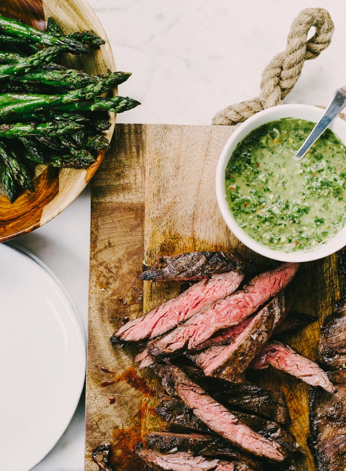 Slices of medium rare grilled steak on a cutting board with a small bowl of italian salsa verde and a large bowl of grilled asparagus on the side.