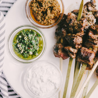 These paleo grilled flank steak skewers are a great party food recipe! Thin strips of grass fed flank steak is charred and crispy on the outside, and and tender on the inside. A real food dipping sauce trio of chimichurri, minty yogurt, and sundried tomato pesto keeps everyone happy. #healthy #wholefood #realfood #paleo #grassfed