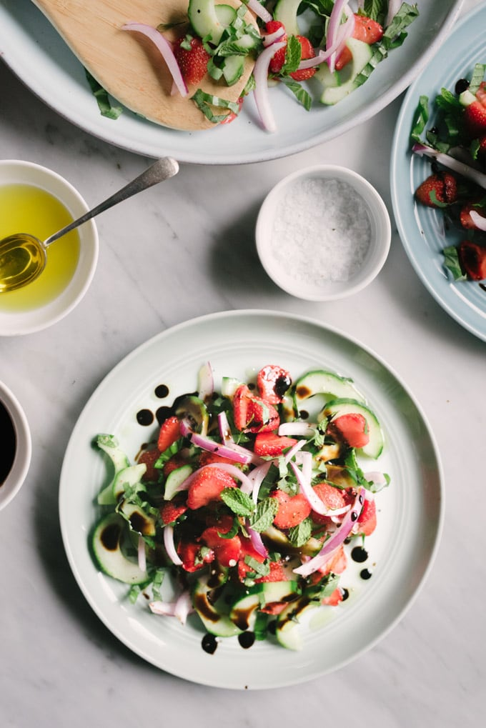 A serving of strawberry cucumber salad drizzled with balsamic reduction and olive oil, and sprinkled with sea salt and cracked black pepper.
