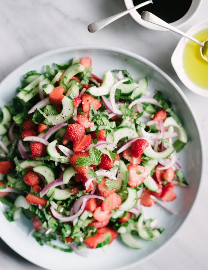 A blue platter with vegan and paleo strawberry cucumber salad on a marble table.