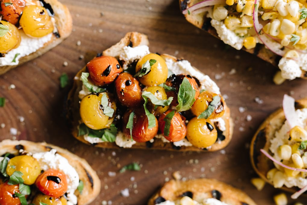 A slice of grilled toast topped with ricotta cheese, burst tomatoes, fresh basil, salt, and pepper.