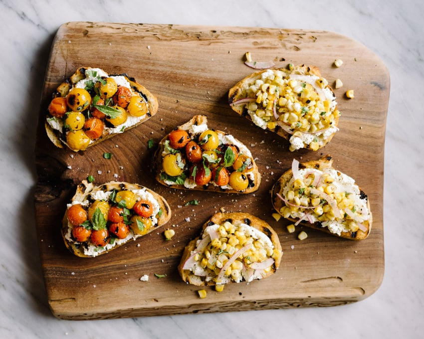 Slices of ricotta toast on a cutting board, half topped with burst tomatoes and basil, and half topped with corn salsa.
