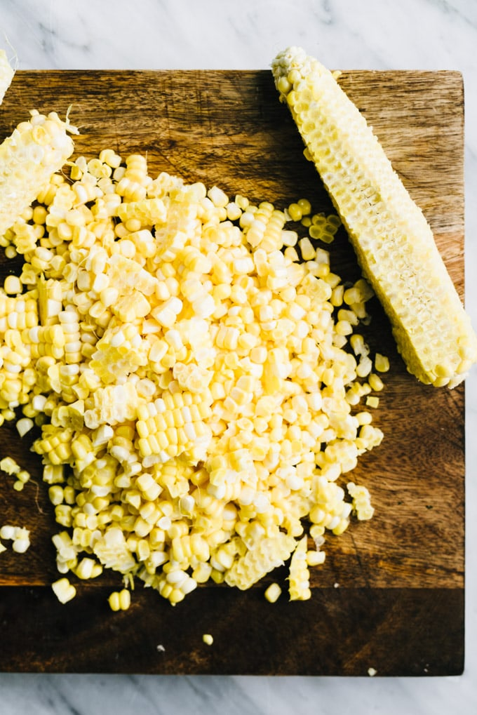 A pile of fresh corn kernels sliced from several ears of corn on a cutting board.