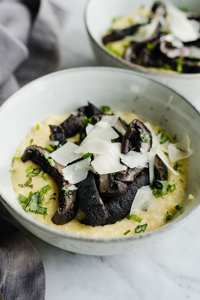 A bowl of polenta topped with charcoal grilled portobello mushrooms, topped with shaved parmesan cheese.