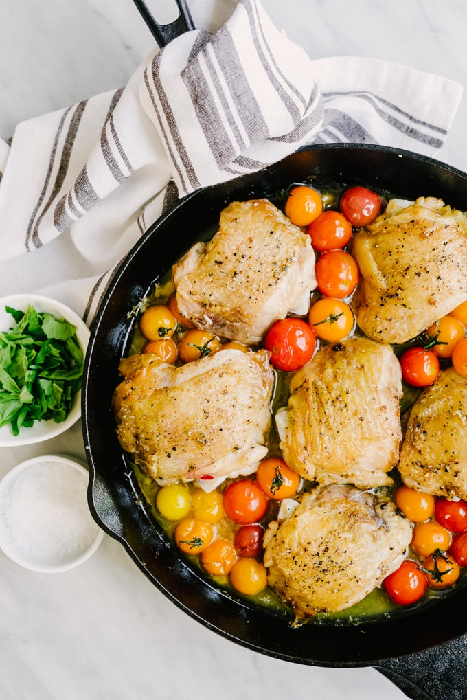 Crispy chicken thighs with burst tomatoes in a cast iron skillet, an easy and family friendly summer paleo recipe.