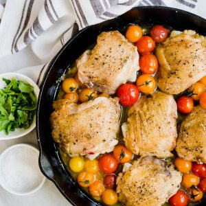 Crispy chicken thighs with burst tomatoes in a cast iron skillet.