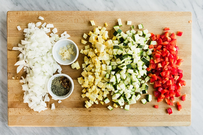 How to make paleo ground turkey hash. Diced onions, summer squash, and peppers with minced garlic and dried herbs displayed on a wooden cutting board.