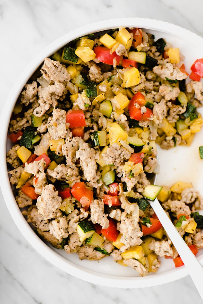 Ground turkey hash with summer squash and bell peppers in a white bowl on a marble background. A fast and easy paleo ground turkey recipe!