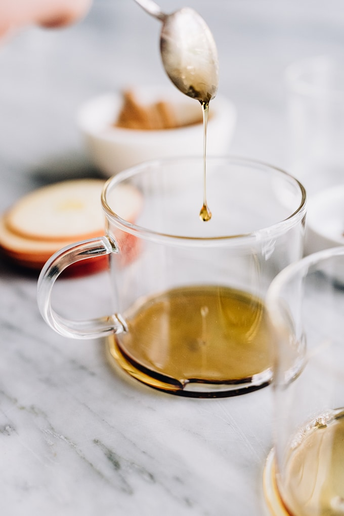 A silver spoon drizzling maple syrup into a glass mug to sweeten an apple cider hot toddy.
