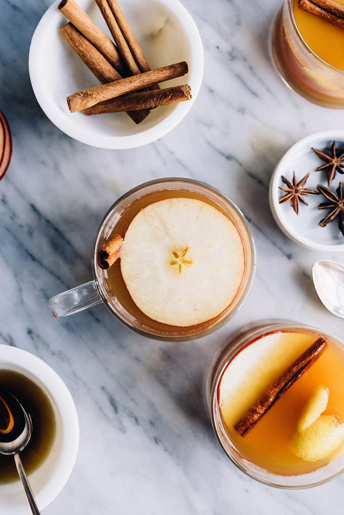 Several mugs filled with an apple cider hot toddy bourbon cocktail surrounded with small bowls of cinnamon sticks, maple syrup, and start anise.