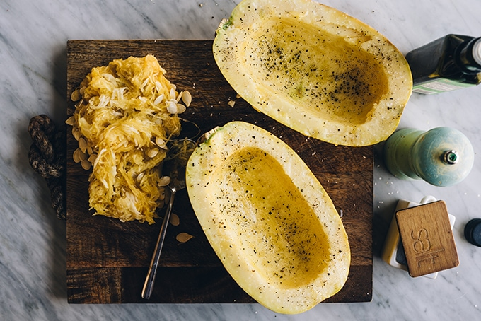 How to roast spaghetti squash. Raw spaghetti squash, halved and dressed with olive oil and salt and pepper. Ready to be roasted and served with crockpot bolognese. Easy, gluten-free pasta substitution.