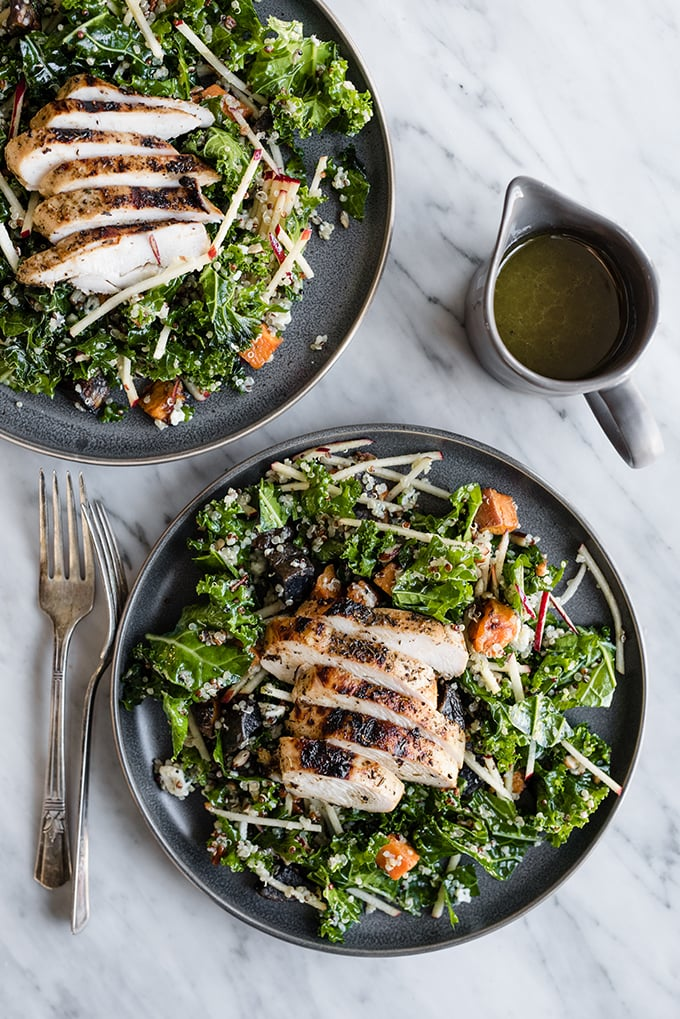 Two kale chicken salads with warm potatoes and apples on grey plates with dressing and vintage silver forks on the side.
