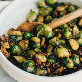 Maple bacon brussels sprouts with bourbon and pecans in a white serving bowl with a wood serving spoon.