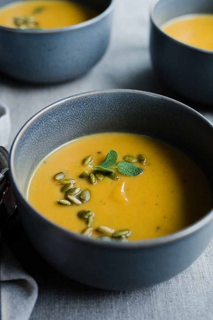 A bowl of healthy pumpkin soup with coconut milk made with fresh roasted sugar pumpkins, fresh herbs, and classic fall spices.