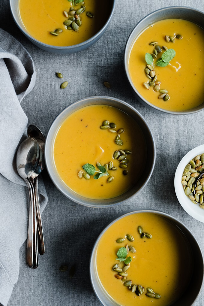 Four bowls of healthy roasted pumpkin soup made with coconut milk, fall spices, fresh herbs, and garnished with pepitas.