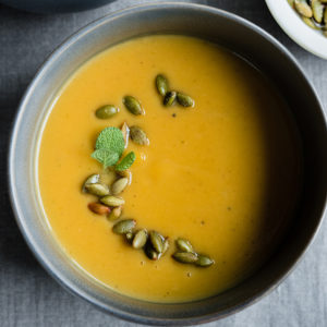 A bowl of roasted pumpkin soup. This healthy paleo soup is made with coconut milk, bone broth, and fall herbs and spices.