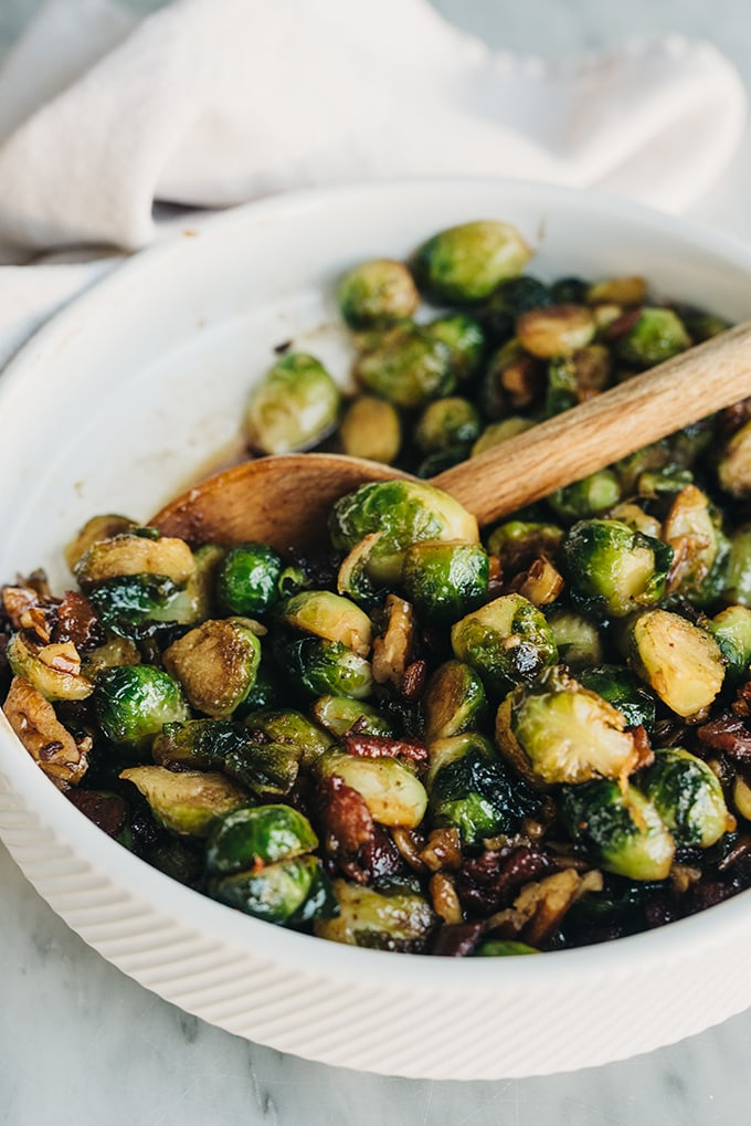 A detail image of maple bourbon bacon brussels sprouts in a white bowl with a wooden spoon and cream towel in the background.
