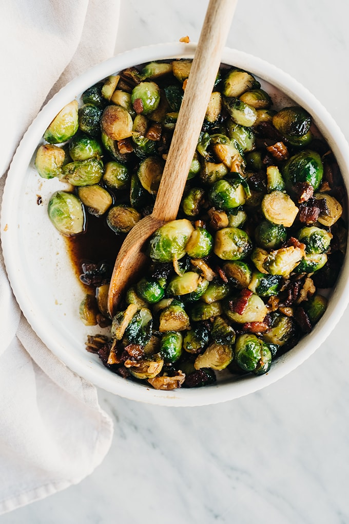 An overhead image of bacon brussels sprouts with maple bourbon glaze in a white serving dish with a wooden spoon.