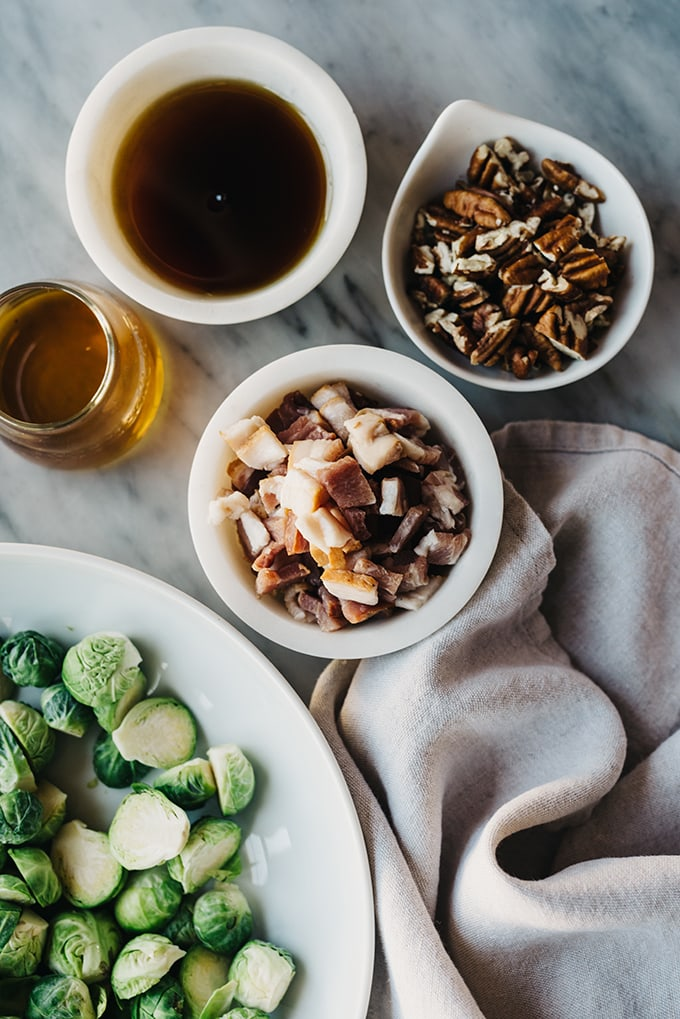 A detail image of maple bourbon bacon brussels sprouts ingredients - small bowls filled with maple syrup, chopped pecans, diced bacon, a small cup of bourbon, and raw brussels sprouts on a marble table.