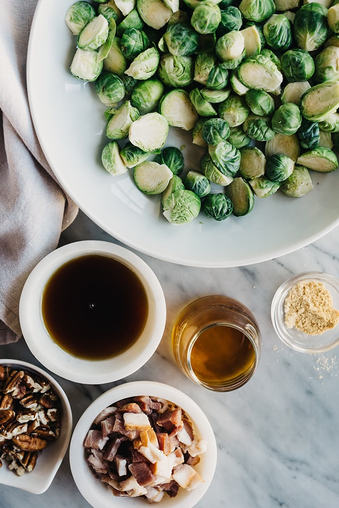 Spread of ingredients to make bacon brussels sprouts - a bowl of raw brussels sprouts, maple syrup, bourbon, diced bacon, raw pecans, and mustard powder.