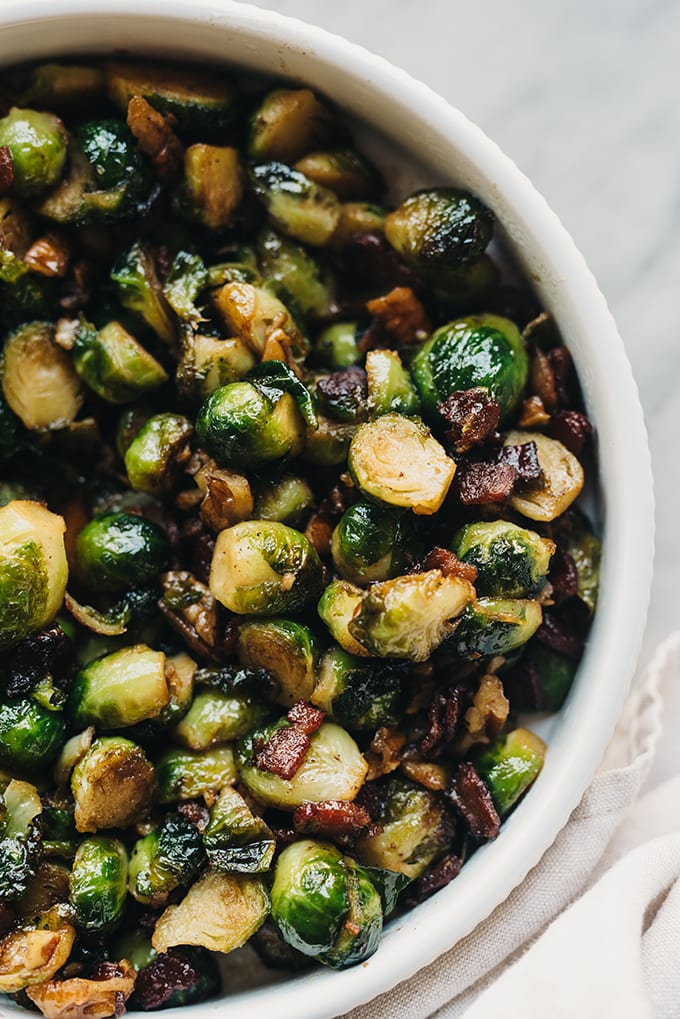 A white ceramic bowl filled with bacon brussels sprouts with maple bourbon glaze.