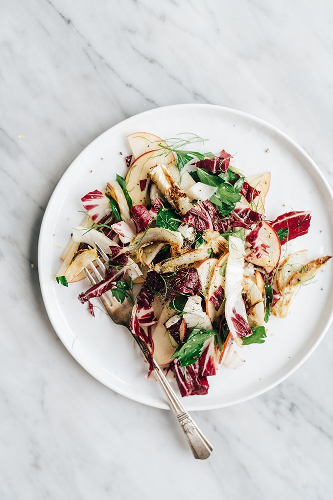 Roasted fennel salad with radicchio and crisp apples on white plate against a marble background.