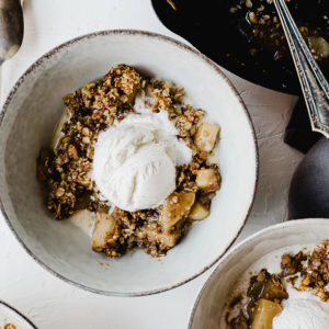 This gluten free apple crisp is a lightened up and refined sugar free version of the Thanksgiving classic! It's sweetened with maple syrup and coconut sugar, and topped with gluten free oats, pecans, and walnuts. It's made start to finish in a cast iron skillet resulting in an equally tender and crisp texture. This is a healthy fall dessert recipe that will satisfy even the pickiest sweet tooth around your table. #glutenfree #sugarfree #applecrisp #thanksgivingdessert #falldessert