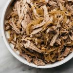 Slow cooker apple cider pulled pork in a white serving bowl on a marble table.