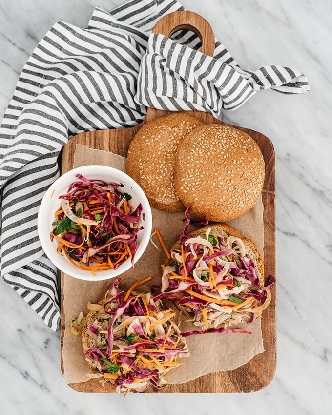 Apple cider pulled pork sandwiches with autumn slaw on a cutting board with a grey and white striped napkin.