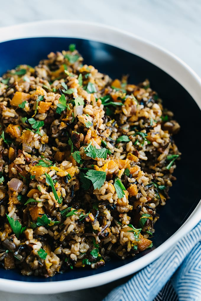 Honeynut squash pilaf with wild rice, fresh herbs, and orange juice and zest in a blue and white serving bowl.