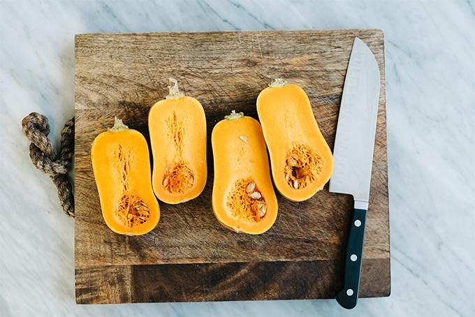 Honeynut squash sliced in half on a wood cutting board.