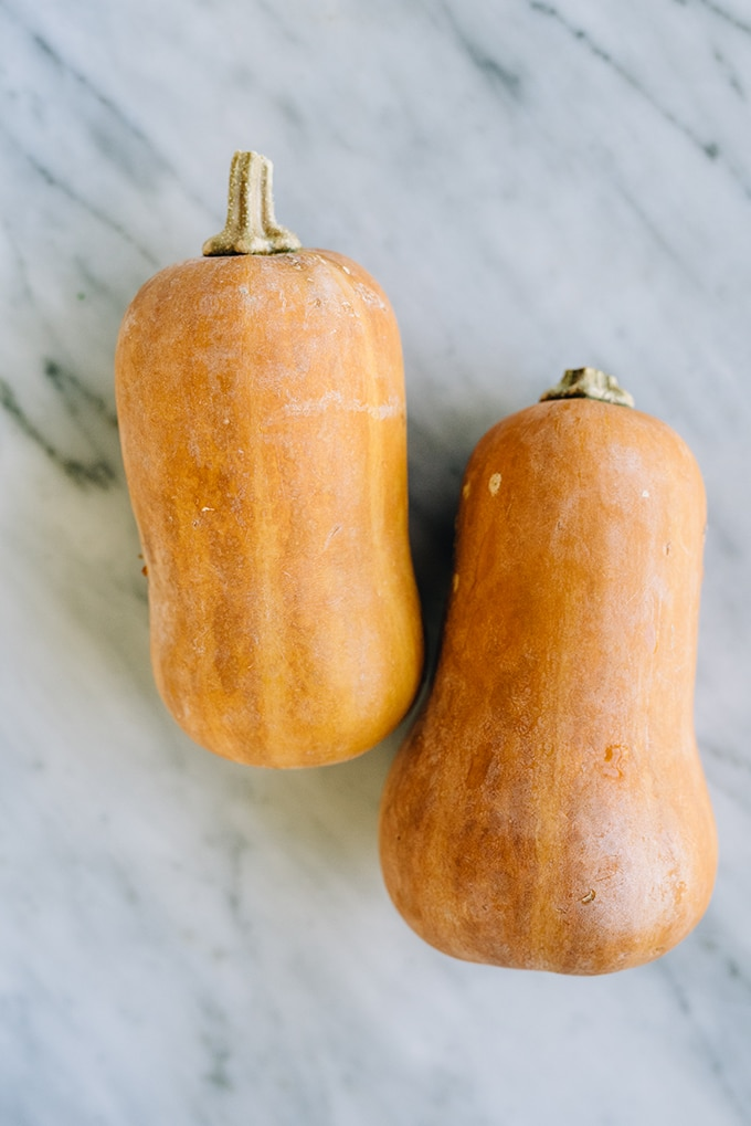 Two mini honeynut squash on a marble countertop