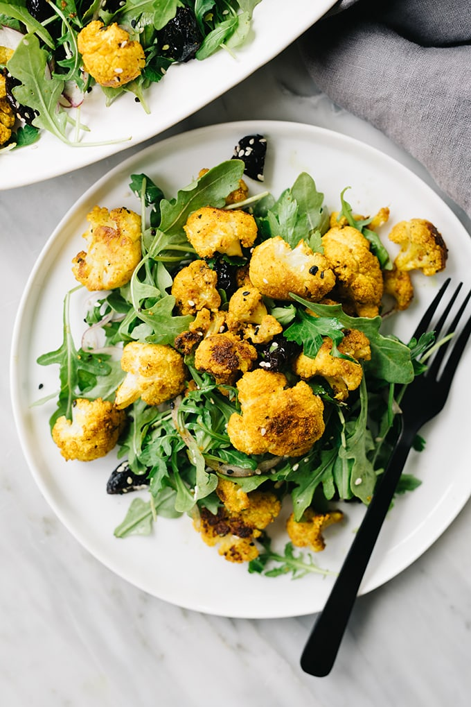 A plate of roasted cauliflower salad with turmeric spice.