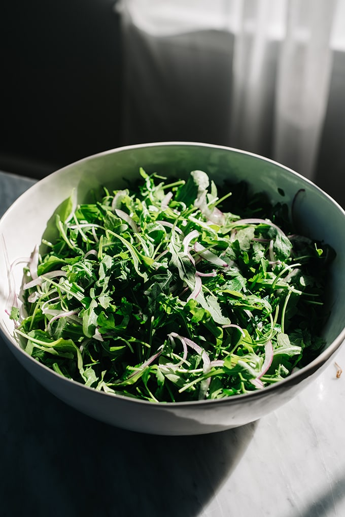 A bowl of arugula and thinly sliced red onion on a marble table next to a window with light streaming through.