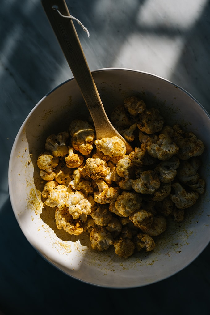 A large bowl of cauliflower florets tossed with turmeric and olive oil.