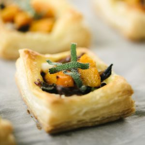 Baked mini butternut squash tart with ricotta cheese and caramelized onions on a baking sheet.