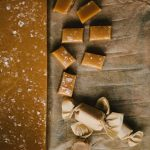 Squares of homemade salted caramels on a piece of parchment paper.