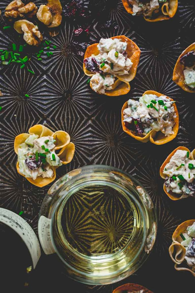 Mini chicken salad bites on a baking sheet with a glass of white wine - an easy, fast, make ahead cocktail party appetizer or hors d'oeuvre.
