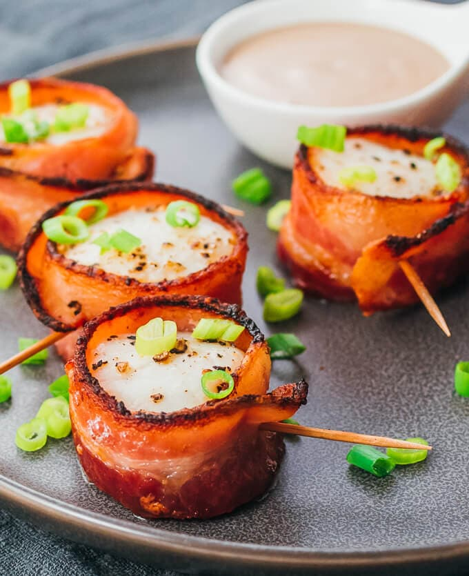 Bacon wrapped scallops on a grey plate with dipping sauce - an easy and fast cocktail party appetizer or hors d'oeuvre.