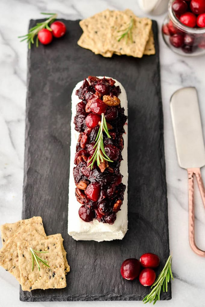 Cranberry and herb goat cheese log on a slate board with crackers - an easy, fast, make ahead cocktail party appetizer or hors d'oeuvre.