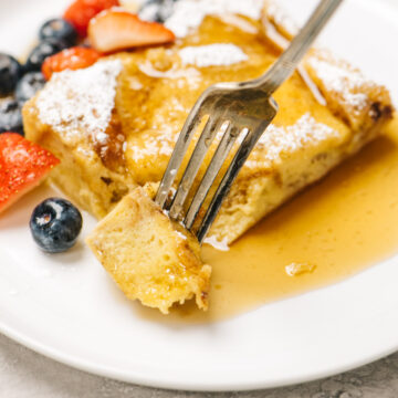 A woman's hand taking a bite of french toast casserole with a vintage silver fork.