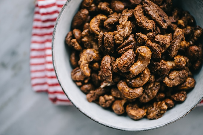 A bowl of paleo and sugar free gingerbread spiced nuts with a red and white linen napkin.
