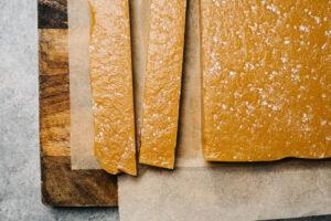 Caramel candy cut into long strips on a cutting board.