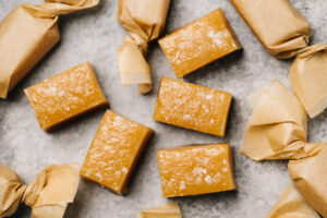 Several wrapped and unwrapped caramel candies on a concrete background.