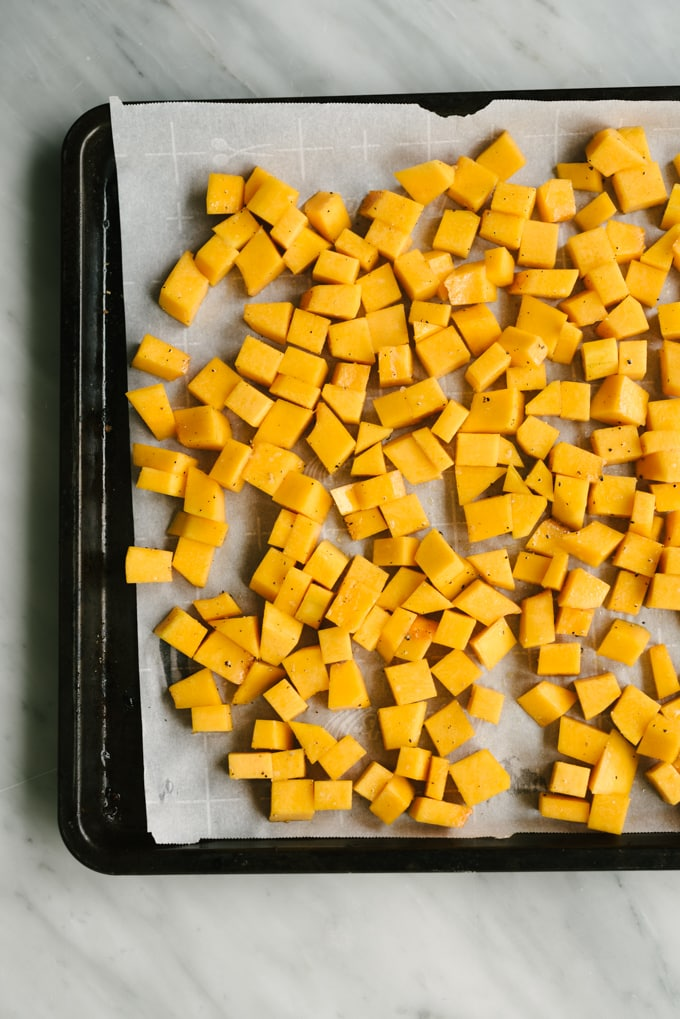 Diced butternut squash on a baking sheet ready to be roasted.