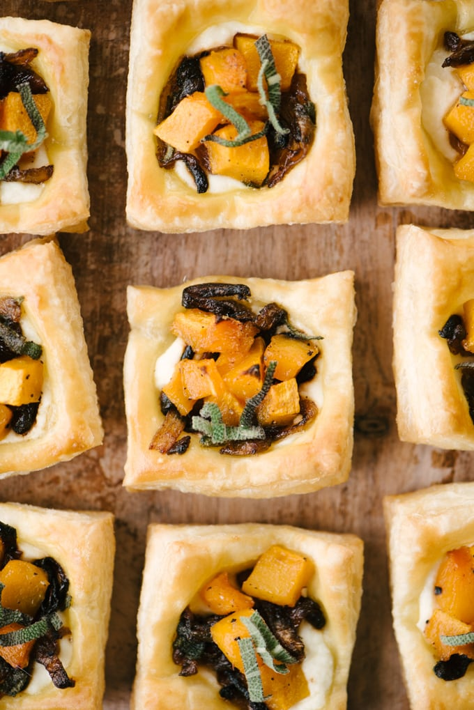 Mini butternut squash tart cocktail party hors d'oeuvres on a wood surface.