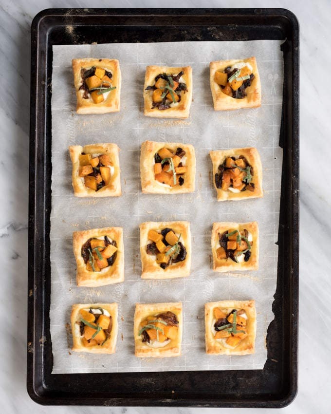 Puffed up and golden brown mini tarts on a baking sheet topped with butternut squash, caramelized onions, and ricotta cheese.