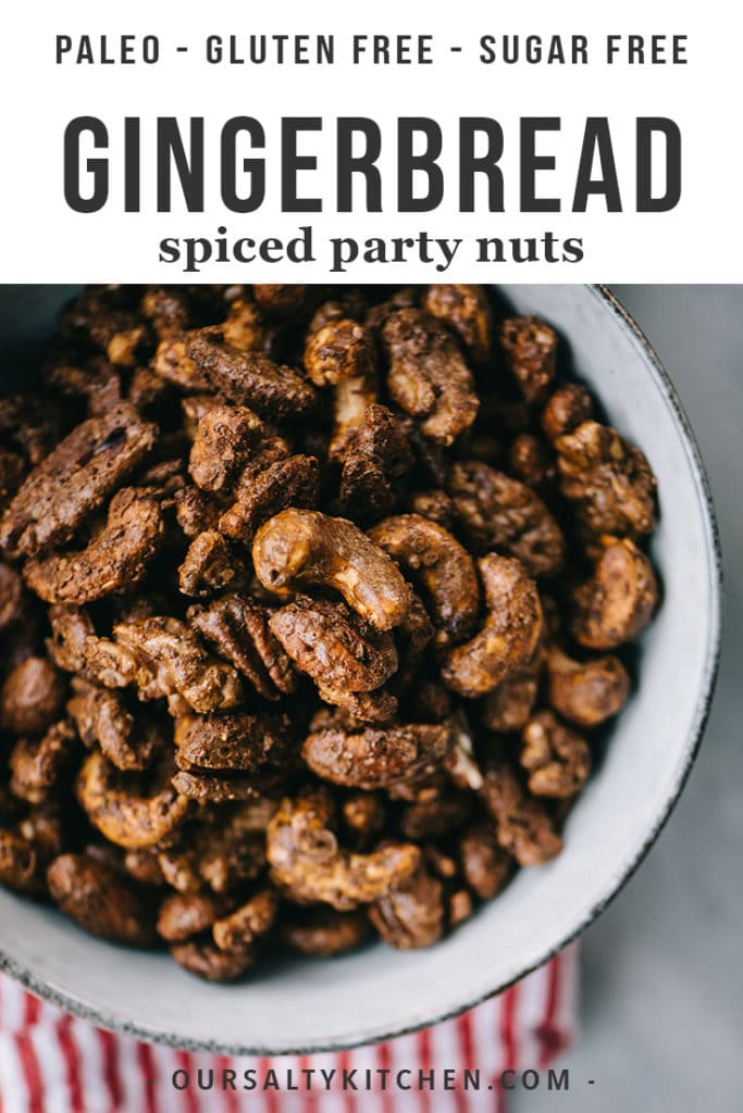 A bowl of gingerbread spiced nuts with a red and white striped napkin.