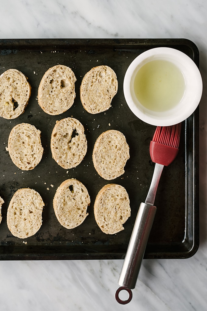 How to make rosemary marinated white bean bruschetta. Slices of whole grain baguette on a baking sheet brushed with olive oil.